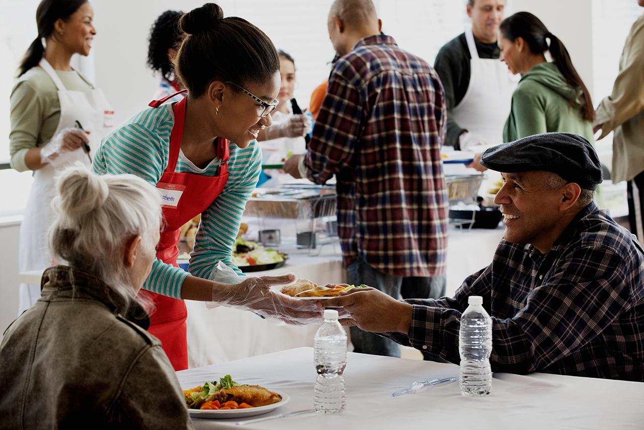 Volunteer serving food at community kitchen